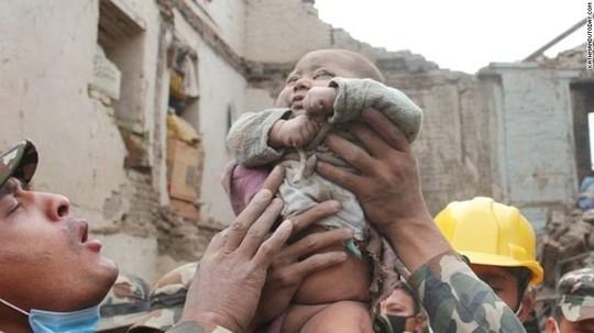 Một binh sĩ Nepal kéo đứa trẻ ra khỏi đống đổ nát trong sự vui mứng của tất cả những người có mặt. Ảnh: Kathmandu Today