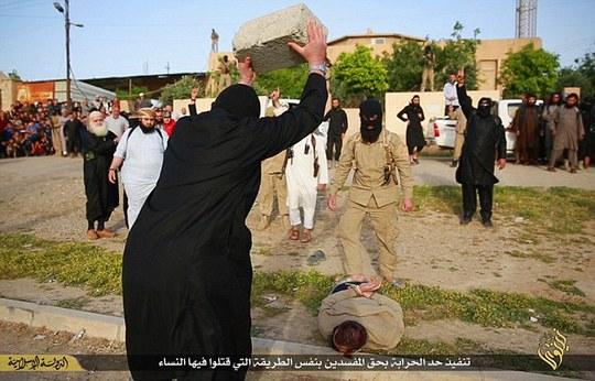 Một tay súng IS ném bê-tông vào đầu phạm nhân. Ảnh: Daily Mail
