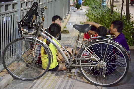 Một nhóm bạn trẻ dùng xe đạp chắn ngang đường để bày đồ ăn uống.