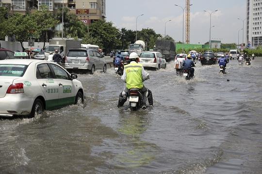 Nước ngập hơn nửa bánh xe khiến các phương tiện di chuyển gặp nhiều khó khăn.