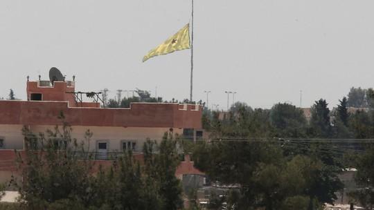 Lá cờ của YPG cắm gần biên giới Syria - Thổ Nhĩ Kỳ. Lực lượng này mới phát hiện 400 m đường hầm do IS đào tại biên giới hai nước. Ảnh: AP