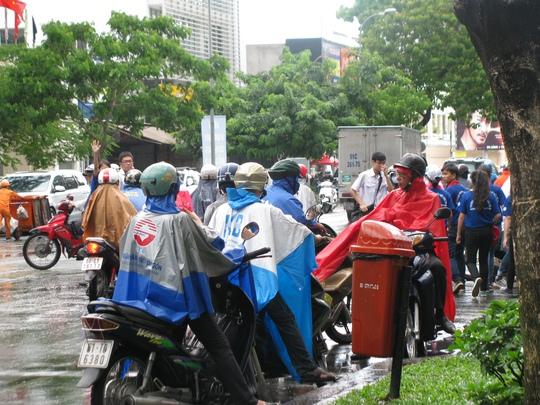Phụ huynh đội áo mưa đứng trước hội đồng thi