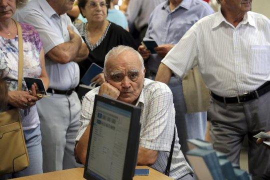 Người đàn ông chờ nhận lương hưu bện trong một chi nhánh của Ngân hàng Quốc gia Hy Lạp. Ảnh: Reuters
