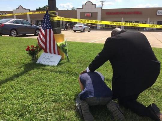 Hai người đàn ông cầu nguyện bên ngoài hiện trường vụ nổ súng hôm 16-7. Ảnh: Reuters