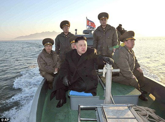 Maximum alert: Pictured on a boat near the western sea border with South Korea, Kim urged front-line troops to be on maximum alert for a potential war in March 2013