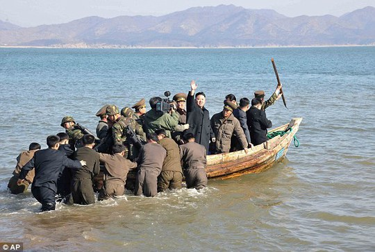 Ahoy! Kim waves at military officers after inspecting the Wolnae Islet Defense Detachment, North Korea, near the western sea border with South Korea in March 2013