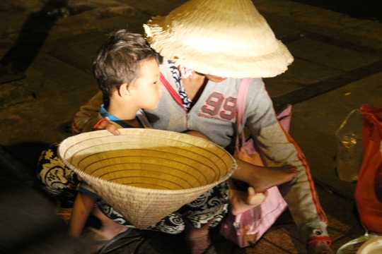 Cảnh người phụ nữ bồng bế trẻ em lao ra đường để xin tiền.