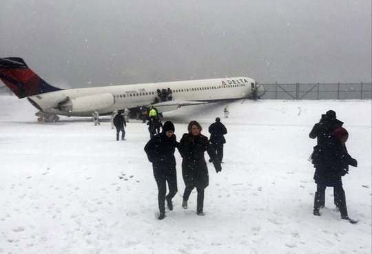 CLICK IMAGE for slideshow: Passengers walk from a Delta jet which skidded off the runway at Laguardia airport in a photo provided by New York Giants N...