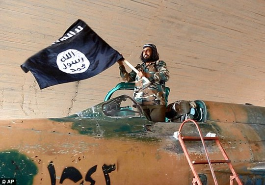 An Isis fighter waves the groups flag from inside a captured government fighter jet in Raqqa