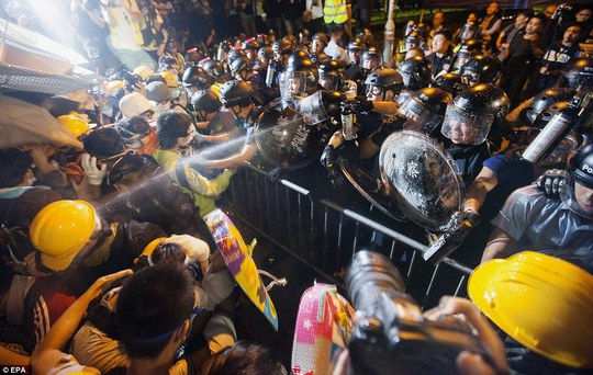 Clashes: Riot police spray a dispersal agent at pro-democracy student protesters outside the office of the Hong Kong Chief Executive today