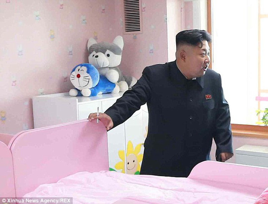 Photobomb: Kim was oblivious to the pair of cuddly toys placed in a compromising position on a wardrobe behind him as he visited an orphanage in Pyongyang in October last year