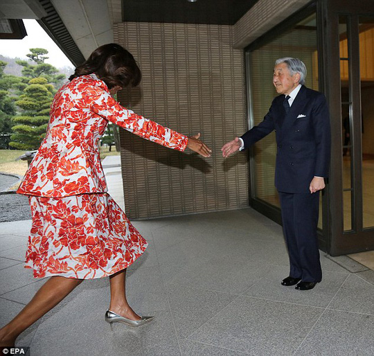 Im going in: Michelle Obama stumbles as she attempts an awkward combination of curtsey, western handshake and Japanese bow when meeting Emperor Akihito in Tokyo. Matters were not helped by the fact that she towers over him
