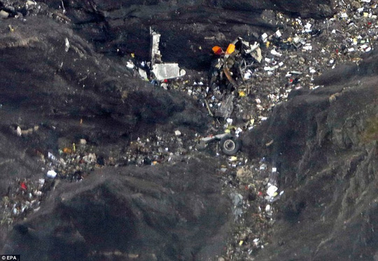 Crash site: Pieces of debris, including what appear to be parts of the aircrafts tail fin and a wheel, are seen strewn on the mountainside