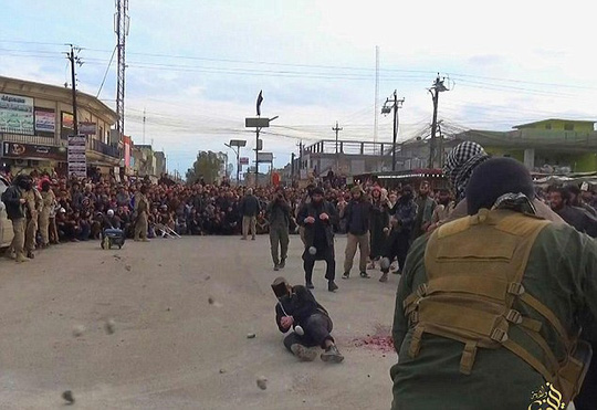 Stoned to death: Taken in the ISIS-stronghold of Mosul in Nineveh province, the shocking images show a large crowd gathered to watch the ISIS militants murder the defenceless couple