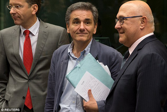 Naive: In only his second day in the job, Tsakalotos (centre) posed for photographs alongside Dutch finance minister and Eurogroup president, Jeroen Dijsselbloem (left) but failed to conceal his notes