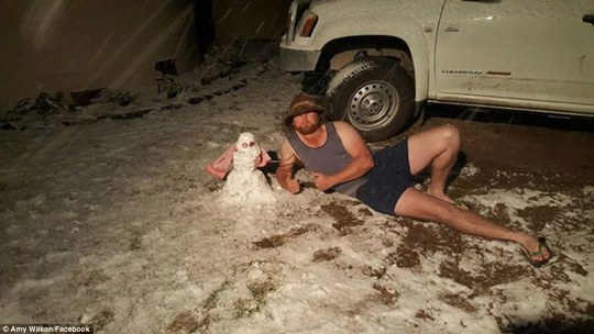 A brave Stanthorpe local builds a snowman in the uncharacteristically cold weather in only a singlet, shorts and thongs