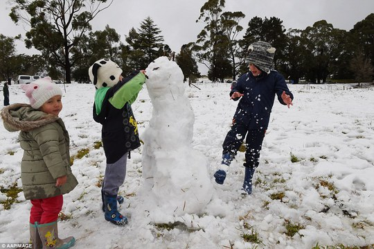 Beau, Lily and Noah Bartolo rugged up to build a snowman in Mittagong n