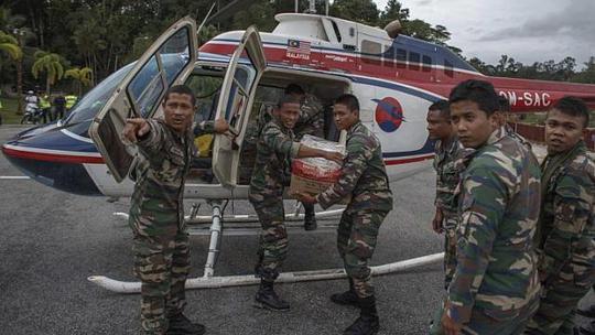 Quân lính Malaysia đang chuyển hàng lên trực thăng cứu trợ. Ảnh Reuters