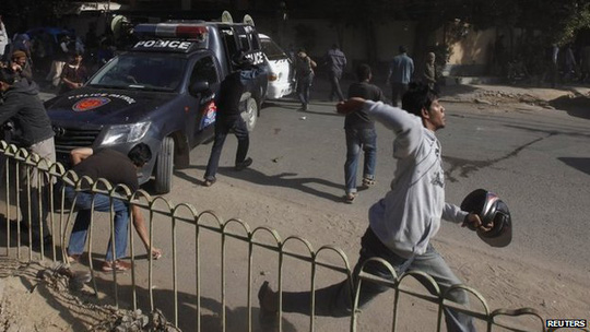 A protester throws stones with others at policemen during a protest in Karachi January 16