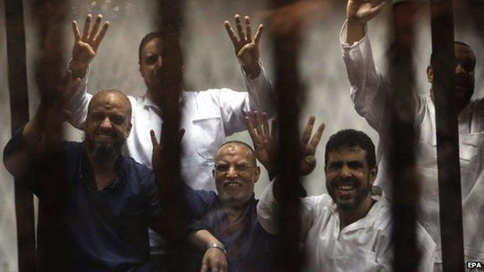 Members of the banned Muslim Brotherhood, Essam al-Erian (C) and Mohamed al-Beltagy (L) along other defendants flash the four-finger sign from behind bars during a trial session, in Cairo, Egypt, 21 April 2015.