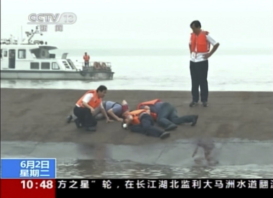 In this image taken from video released by Chinas CCTV, rescue workers listen for a response to their tapping on the hull of a capsized ship on...