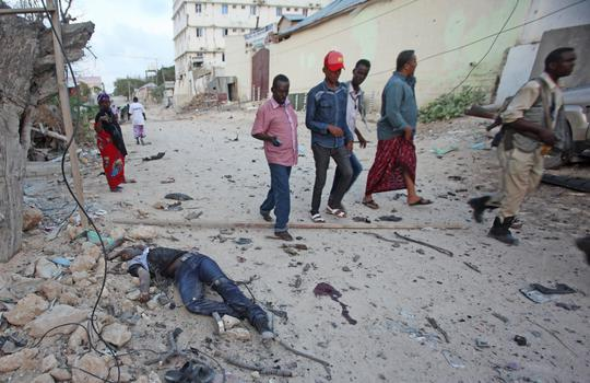 Somalis walk past a dead civilian outside the hotel who was killed after a car bomb that was detonated at the gate of a hotel in Mogadishu, Somalia , Friday, March, 27, 2015,, A Somali police official says a suicide bomber has detonated his explosives-laden car at the gate of a hotel popular with government officials in Mogadishu. Capt. Mohamed Hussein says gunfire could be heard inside the Maka-Mukarramah Hotel, but it was not clear if any gunmen had managed to penetrate the hotels gate( AP Photo/Farah Abdi Warsameh)