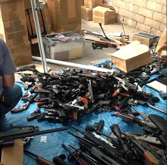 Police inspect some of the 1,200 guns found in the condo of a man who was decomposing in a car down the street for about two weeks.