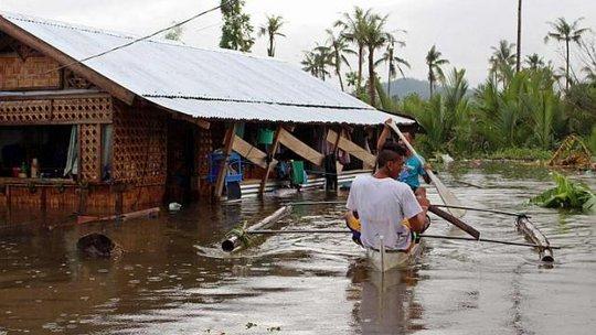 Người dân tại thị trấn Palo, tỉnh Samar, Philippines chống trọi với lũ lụt. Ảnh Reuters