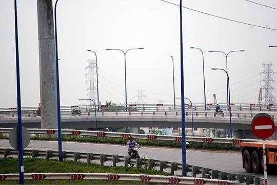 Một người điều khiển xe máy di chuyển từ cầu vượt Cát Lái qua đường Mai Chí Thọ