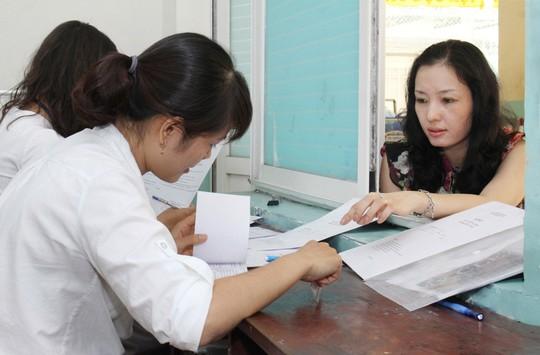 Phụ huynh nộp hồ sơ xét tuyển vào lớp 6 Trường THCS Nguyễn Du (quận 1, TP HCM) Ảnh: HOÀNG TRIỀU