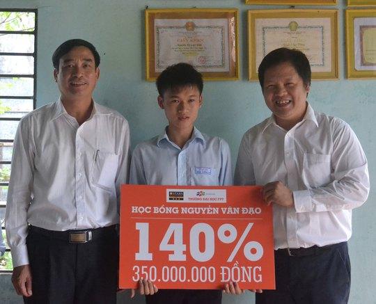 Ông Đàm Quang Minh, Hiệu trưởng Trường ĐH FPT (bìa phải) và Giám đốc Sở GD-ĐT Đà Nẵng, ông Lê Trung Chinh, trao học bổng cho em Nguyễn Ngọc Dưỡng Ảnh: HỒNG QUANG
