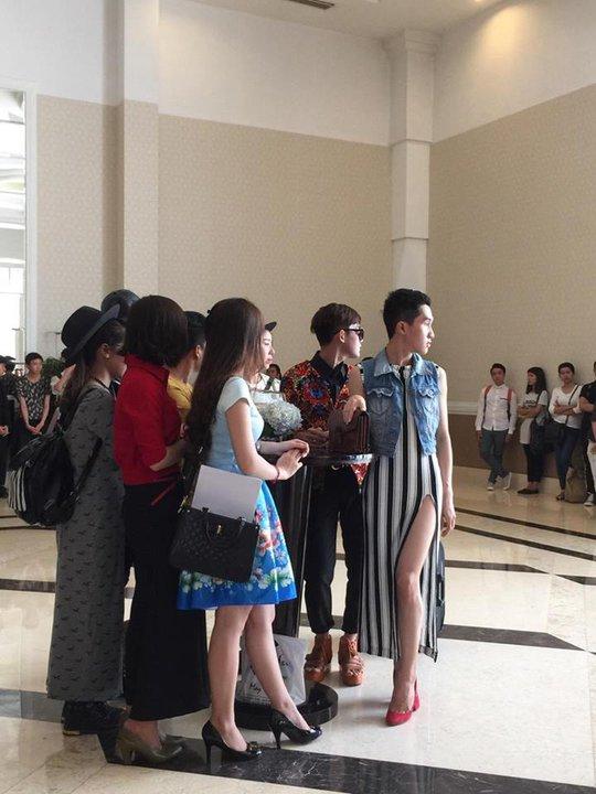Một người mẫu nam diện đầm kiểu nữ đi theo hỗ trợ thí sinh. Ảnh: Facebook