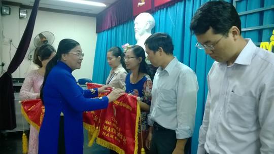 Bà Nguyễn Thị Bích Thủy, Phó Chủ tịch LĐLĐ TP HCM, trao cờ thi đua cho các đơn vị xuất sắc tại quận Tân Phú, TP HCM Ảnh: CAO HƯỜNG