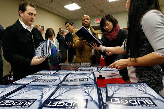 Người dân Mỹ mua đọc đề xuất ngân sách cho tài khóa 2016 của Tổng thống Barack Obama Ảnh: REUTERS