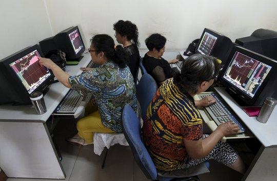 Các nhà đầu tư Trung Quốc theo dõi thông tin chứng khoán trên máy tính ngày 9-7 Ảnh: REUTERS