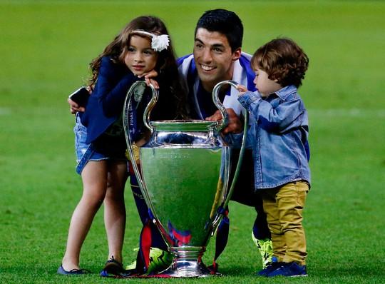 Suarez khoe chiếc cúp vô địch Champions League đầu tiên cùng 2 con Ảnh: REUTERS