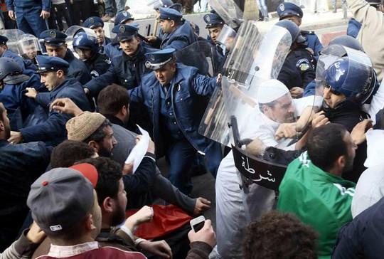 Người biểu tình đụng độ cảnh sát ở TP Algiers - Algeria ngày 16-1 Ảnh: REUTERS