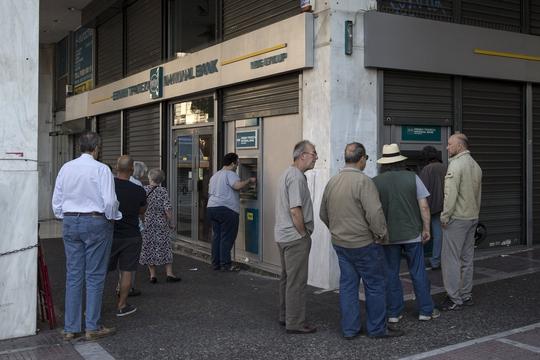 Người dân Hy Lạp xếp hàng trước các máy ATM bên ngoài một chi nhánh Ngân hàng Quốc gia ở Athens ngày 28-6Ảnh: REUTERS