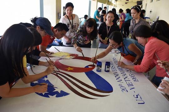 Các nhân viên của Tổng lãnh sự Mỹ tại TPHCM cùng các họa sĩ đang vẽ bức trang sơn dầu khắc họa logo được thiết kế để kỷ niệm 20 năm ngày thiết lập lại quan hệ ngoại giao giữa hai nước. Ảnh: Tổng lãnh sự Mỹ tại TPHCM cung cấp