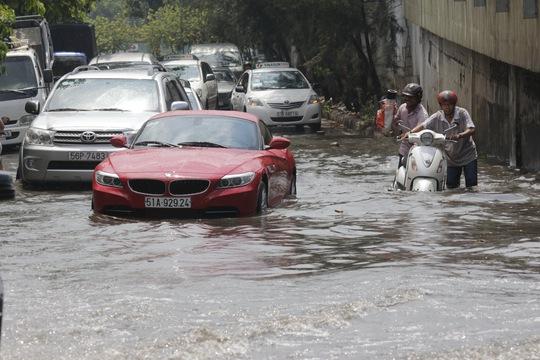 Xe cộ ùn tắc và rối loạn vì nước ngập. Ảnh: Quốc Chiến