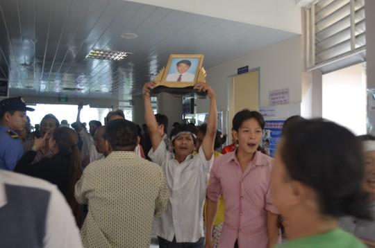 Người thân anh Sang cầm di ảnh anh đòi gặp bác sĩ Đoàn Văn Hùng.