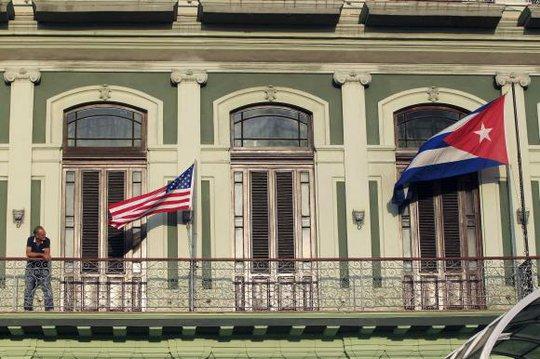 Cờ Mỹ (trái) và cờ Cuba tung bay trước cửa một khách sạn ở thủ đô Havana hôm 19-1. Ảnh: Reuters