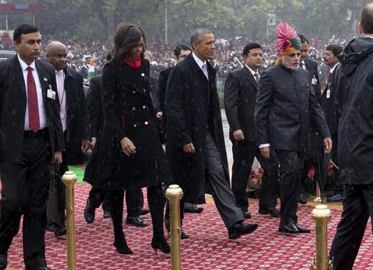 Vợ chồng Tổng thống Obama bất chấp trời mưa vẫn ngồi dự lễ. Ảnh: Reuters