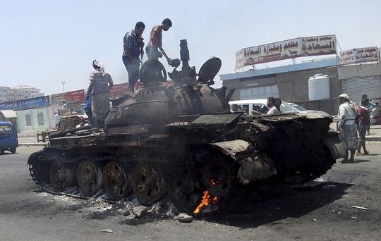 Người dân đứng trên một chiếc xe tăng bị đốt cháy ở TP Aden. Ảnh: Reuters