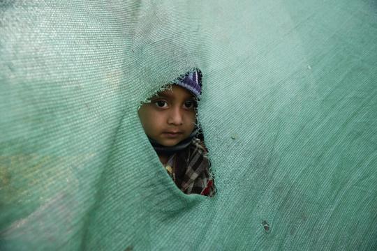 Một em bé thò đầu ra khỏi ngôi lều ở Kathmandu. Ảnh: EPA