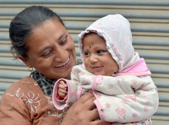 Bà Rasmila Awal bế cậu con trai Sonies sau khi được cứu sống. Ảnh: Splash News