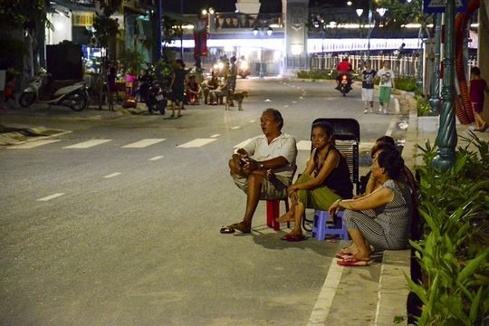 Một gia đình ngang nhiên ngồi giữa đường để hóng mát, bất chấp xe cộ chạy qua.