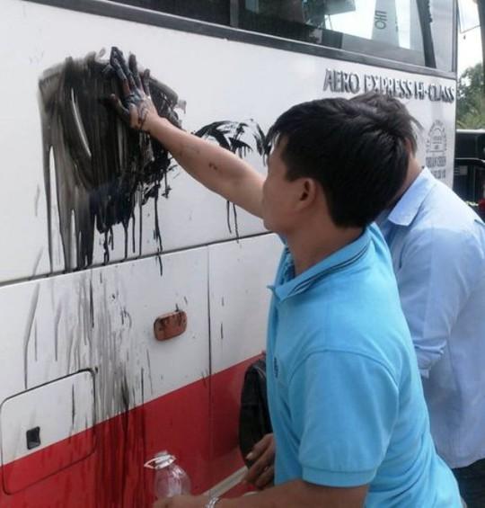 Dùng sơn đen bôi bẩn xe khách du lịch. Ảnh: L.Giang