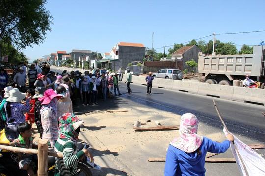 Hàng chục người dân dùng cây gậy, gạch đá ngăn cản việc thảm nhựa dự án mở rộng QL1A. Ảnh: Tử Trực