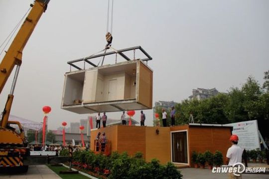 Một nhóm công nhân dựng nhà bằng cần cẩu. Ảnh: CCTV